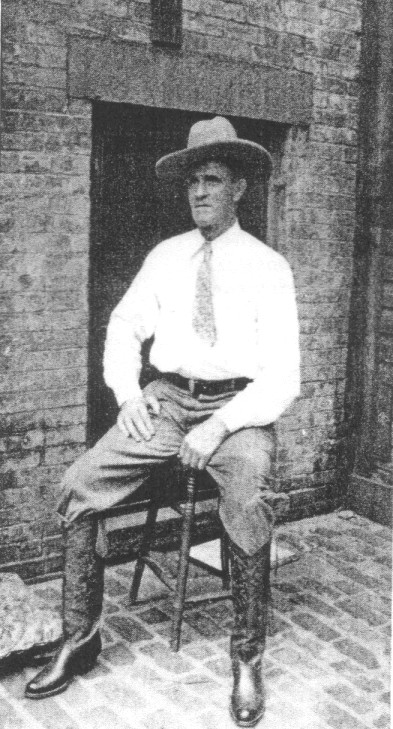 Old West imposter Frank Hopkins poses in his new boots on a milking stool in New York-
