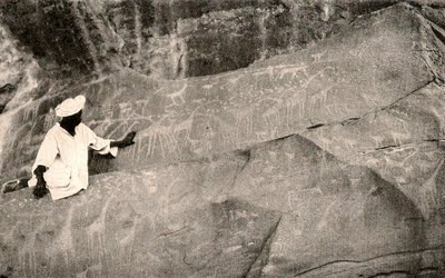 A member of the expedition examines Paleolithic rock carvings indicating the Sahara had once enjoyed a milder climate.