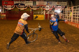 PHOTO 5-1: In the Texas ring, bull-fighter Frank Newsom teaches writer Jim Clash how to handle a charging bull using a mockup wheel. (Photo: Andy Gregory/Humps n Horns Magazine)